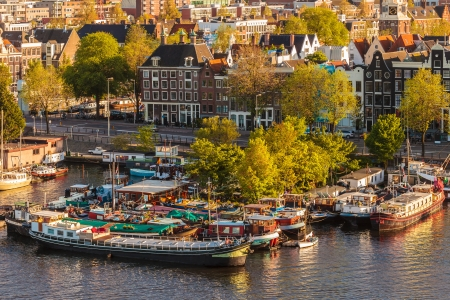 Group of classic ships used as houseboats in Amsterdam during sunset