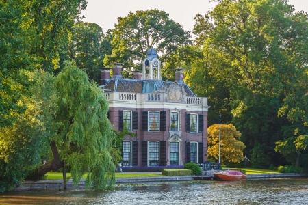 traditionally dutch: BREUKELEN - JULY 7  Historical villa alongside river The Vecht on July 7, 2013 in Breukelen  The Dutch river The Vecht is famous for its historical villas alongside the river side which were traditionally used as summer houses for rich Amsterdam residents