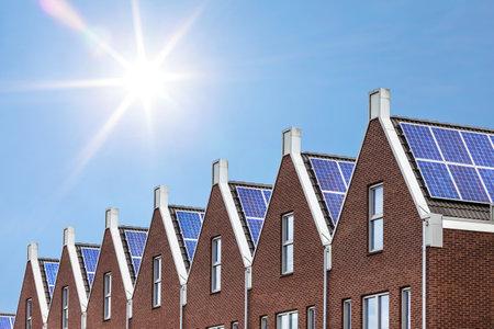 新しく晴れた空に対する屋根に取り付けられた太陽電池パネルと家を建てる