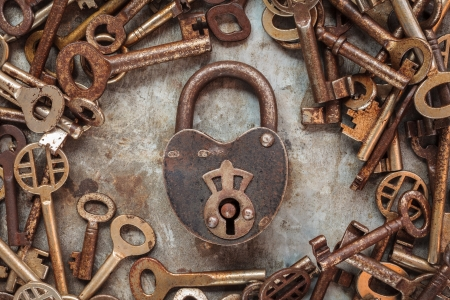 antique keys: Vintage rusty padlock surrounded by old keys on a weathered steel background Stock Photo