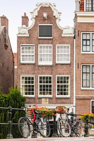 canal house: Vista Sumer delle biciclette su un ponte sul canale di Amsterdam con una antica casa di canale in background Editoriali