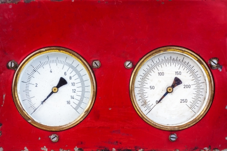 Old red industry panel with two round measurement meters photo
