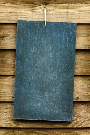 Retro styled image of a hanging chalkboard against a wooden wall photo