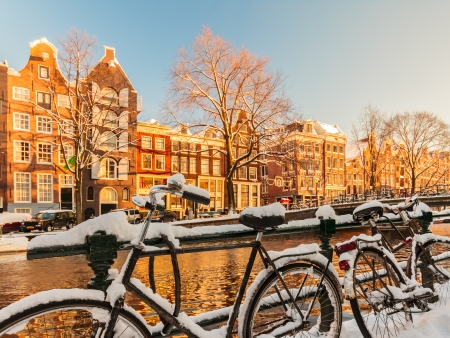 Bicycles covered with snow alongside a canal during winter in Amsterdam
