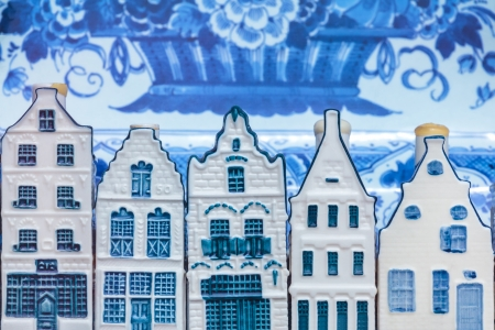 Row of Dutch Delft blue souvenir houses with an antique plate in the background