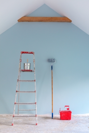 Paint tools with ladder against a newly painted light blue  wall Imagens