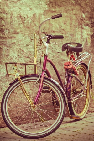 Retro styled image of a colorful bike against an old wall photo
