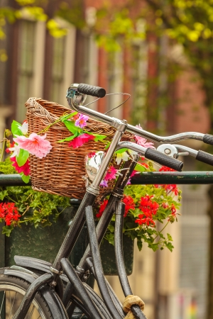 Summer view of bicycles with flowers on a canal bridge in the Dutch city Amsterdam photo
