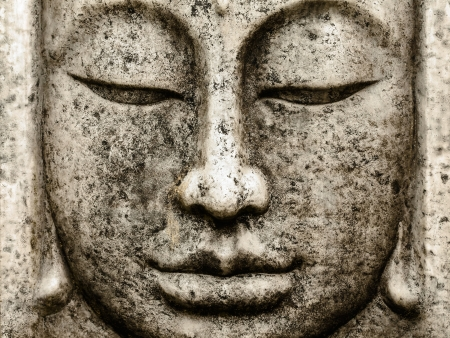 Head of a grey weathered old buddha statue photo