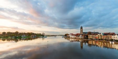 Panoramisch uitzicht op de rivier Nederlandse IJssel met de historische stad Deventer weerspiegeld in het water Stockfoto
