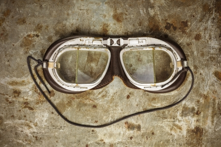 race car driver: Retro styled image of old leather race goggles on a rusty steel background Stock Photo