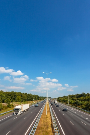 Multiple lane highway in The Netherlands against a blue sky with few clouds Stock Photo