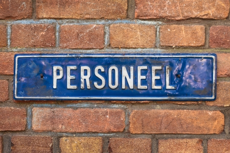 Old dented blue sign with the Dutch text  Personnel  on a brick wall photo
