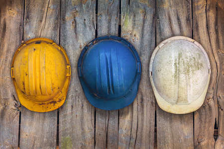 Three vintage construction helmets hanging on an old wooden wall