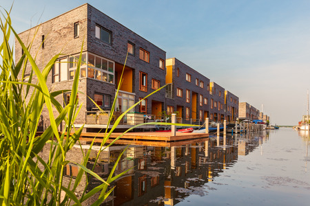 Row of Dutch modern canal houses in Almere reflected in the water photo