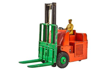 lift truck: Juguete de la vendimia carretilla elevadora tenedor con el trabajador aislado en un fondo blanco