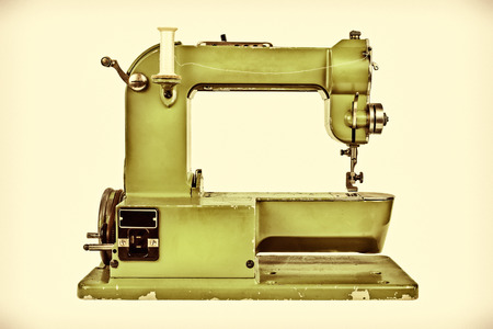 Retro styled image of an old sewing machine against a light sepia background photo