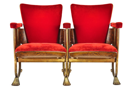 Two vintage red movie theater chairs isolated on a white background