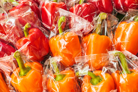 Bunch of plastic wrapped orange and red bell peppers photo