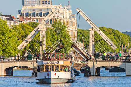 AMSTERDAM, THE NETHERLANDS - MAY 16, 2014  A vintage cruise boat passes the famous Amsterdam Skinny Bridge crossing the Amstel river Editorial