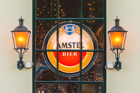 AMSTERDAM, THE NETHERLANDS - MAY 16, 2014  Illuminated sign with the Dutch Amstel Beer logo behind a window of an old Amsterdam pub
