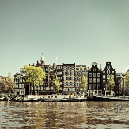 Retro styled image of an Amsterdam canal with house boats and canal houses in the back photo