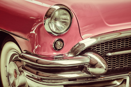 Retro styled image of a front of a pink classic car