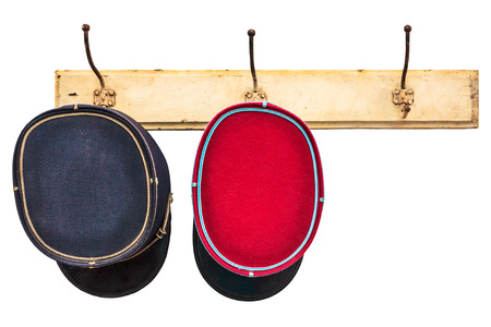 Two vintage conductor hats hanging on a hat-rack isolated on a white background photo