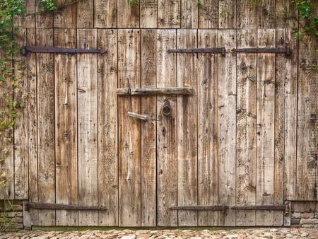 Old weathered wooden barn door with steel hinges