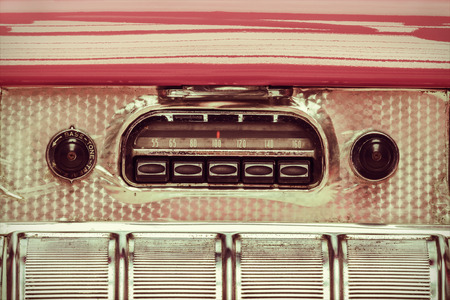 Retro styled image of an old car radio inside a pink classic car photo