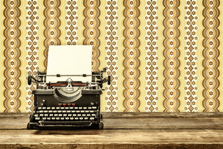 Retro styled image of an old typewriter with blank paper sheet on a wooden table with vintage wallpaper behind it photo