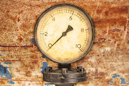 Old industry display mano meter in front of a rusty metal background Фото со стока