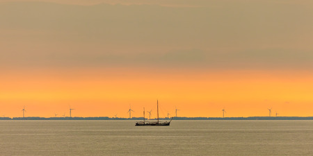 markermeer: Panoramic image of a sailing boat at the Dutch Markermeer during sunset with wind turbines in the background
