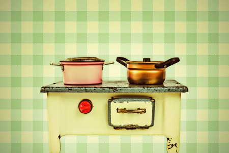 doll house: Retro styled image of a doll house cooking stove with pans in front of vintage wallpaper