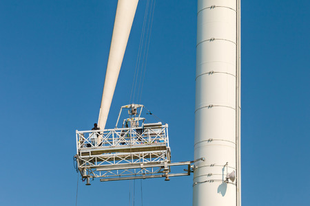 wind mills: Maintenance of a wind turbine against a clear blue sky Stock Photo