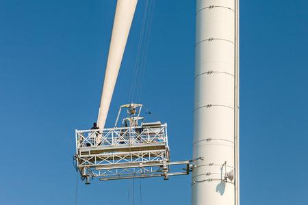 wind turbine: Maintenance of a wind turbine against a clear blue sky Stock Photo