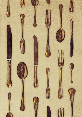 Vintage styled image of old forks, knives and spoons in a repetitive pattern photo