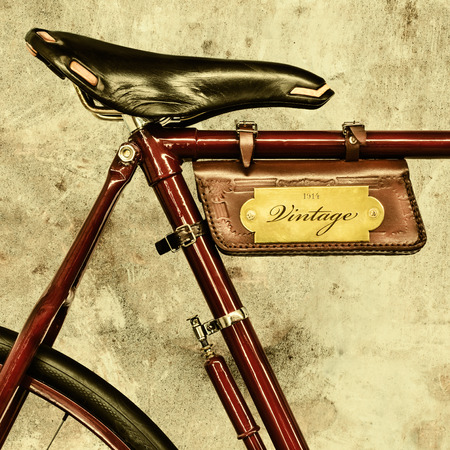 saddle: Detail of a vintage bicycle with leather saddle and bag