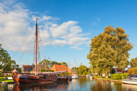 Old wooden sailing boat in a canal in the Dutch village Heeg, Friesland Editorial