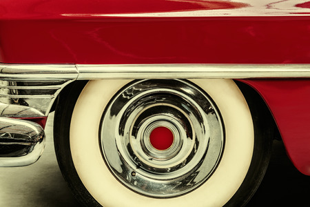 front view: Retro styled image of the wheel of a red vintage American car