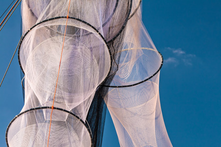 trawler net: New unused hanging fishing nets in Holland against a blue sky Stock Photo