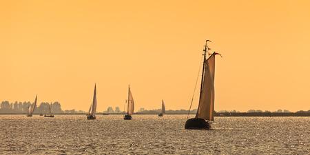 Panoramic image of traditional Frisian Dutch sailing ships during sundown Stock Photo