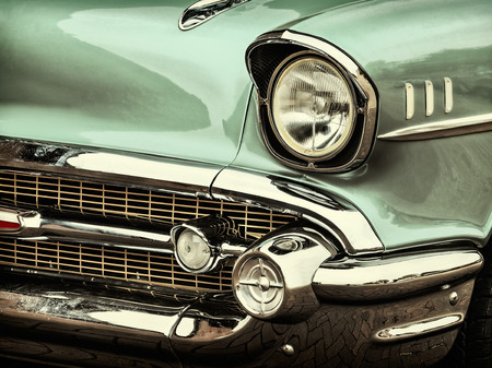 headlights: Retro styled image of a front of a green classic car Stock Photo