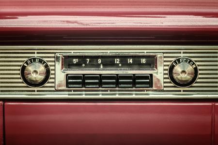 レトロなスタイルの赤の古典的な車の中の古い車のラジオの画像