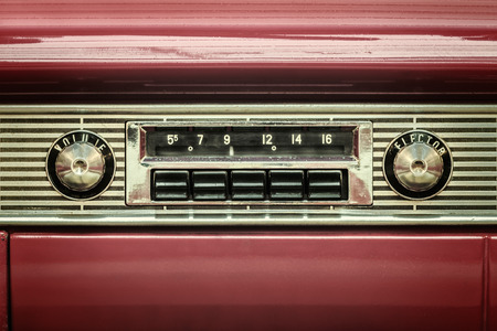 Retro styled image of an old car radio inside a red classic car