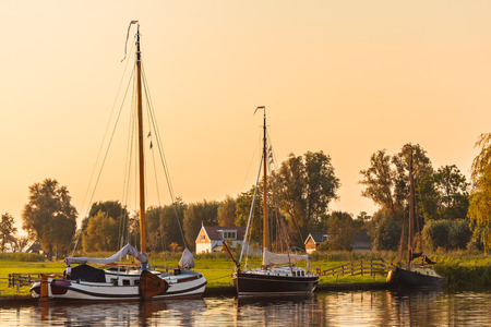 River with sailing boats in the Dutch province of Friesland during sunset