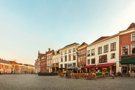 Ancient row of houses with restaurants and bars in the historic Dutch city of Zutphen during sunset