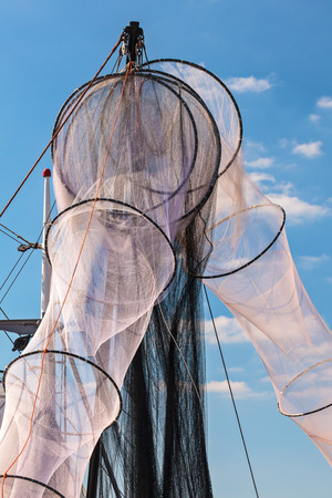 unused: New unused hanging fishing nets in Holland against a blue sky Stock Photo
