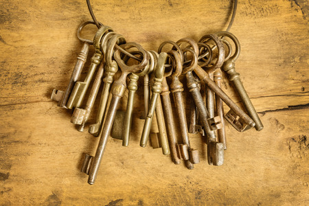 Set of old keys hanging on a ring in front of a wooden background