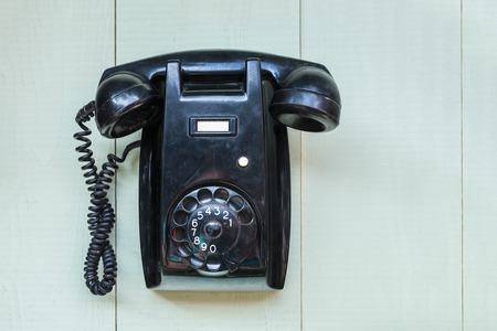 bakelite: Vintage black bakelite telephone hanging on a green wooden wall